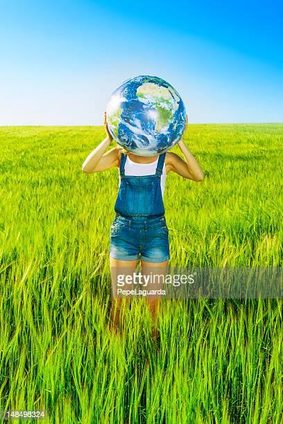 Frau holding Welt Globus in einer grünen Feld