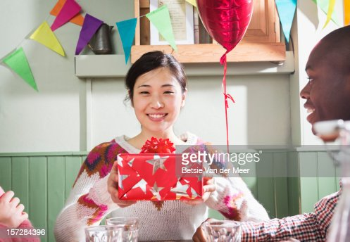 Woman holding wrapped gift, friends in foreground. : Stock Photo