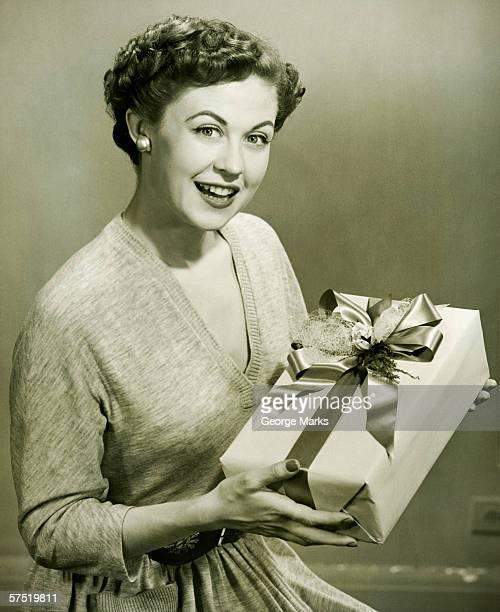 Femme tenant un cadeau enveloppé dans le studio, (B & W), portrait