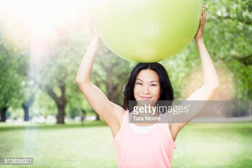 woman holding yoga ball in park