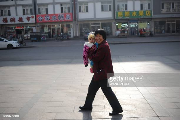 A woman holds a baby as she walks along a road in Tangshan in northern China's Hebei province on November 15 2013 China's Communist rulers announced...