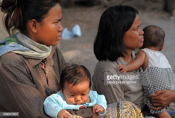 A woman holds a baby at a village on the outskirts of Siem Reap province some 300 kilometers northwest of Phnom Penh on February 22 2011 Rising food...