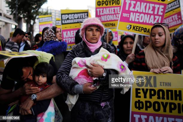 A woman holds a baby in her arms as she and others take part in a demonstration by Greek antifascist groups against the war in Syria and the European...