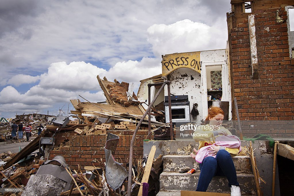 CONTENT] A woman holds a baby near 2509 South Joplin Avenue in Joplin, Missouri, while sitting on the steps of her destroyed home in May 25, 2011.