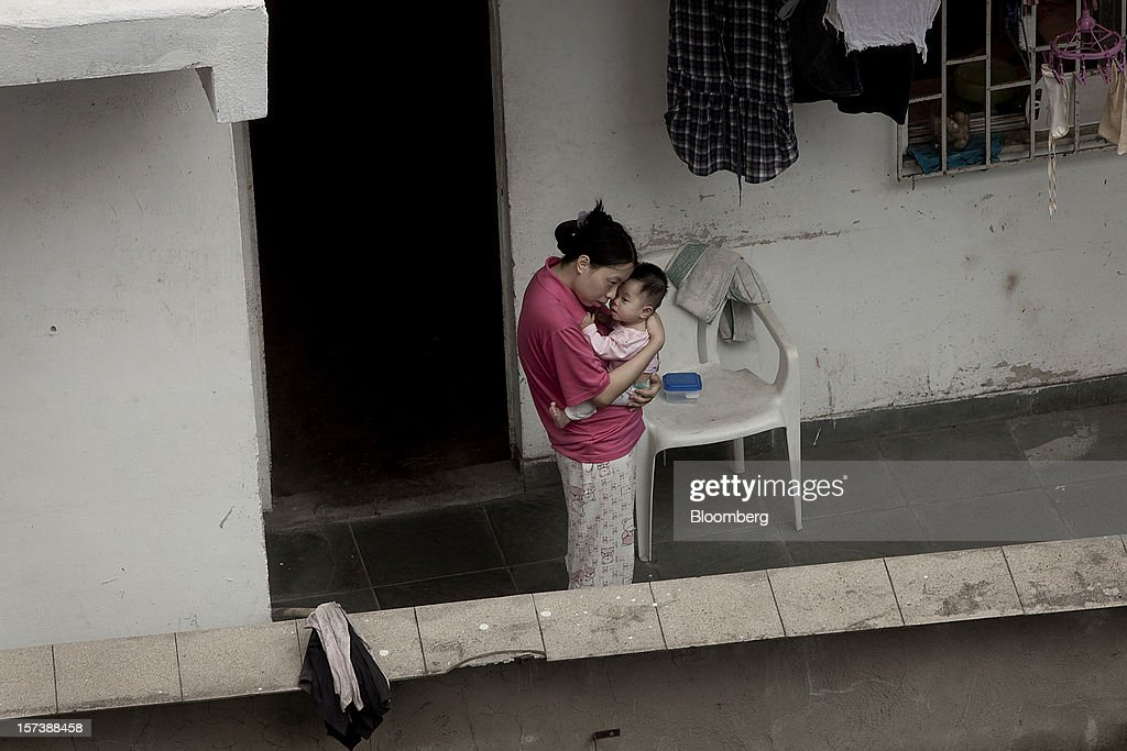 A woman holds a baby on the terrace of a house in the Rocinha slum of Rio de Janeiro, Brazil, on Wednesday, Nov. 28, 2012. About 56 percent of the 12 million people who live in slums like Rocinha were considered middle class in 2011, up from 29 percent in 2001, according to a study this year by Instituto Data Popular, a Sao Paulo-based research group. Photographer: Dado Galdieri/Bloomberg via Getty Images