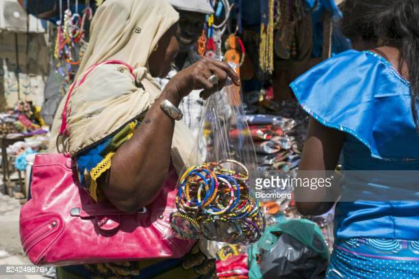 A woman holds a bag of bracelets at the Malian market in the Plateau district of Dakar Senegal on Friday July 28 2017 Senegalese voters will elect a...