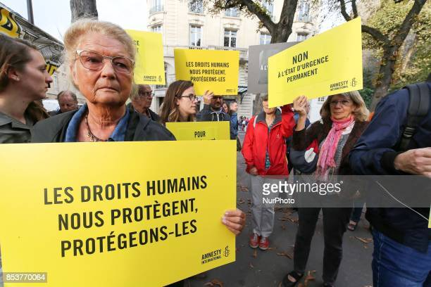 A woman holds a bag reading 'Human rights protect us let us protect them' during a protest against 'permanent state of emergency' in Paris on...