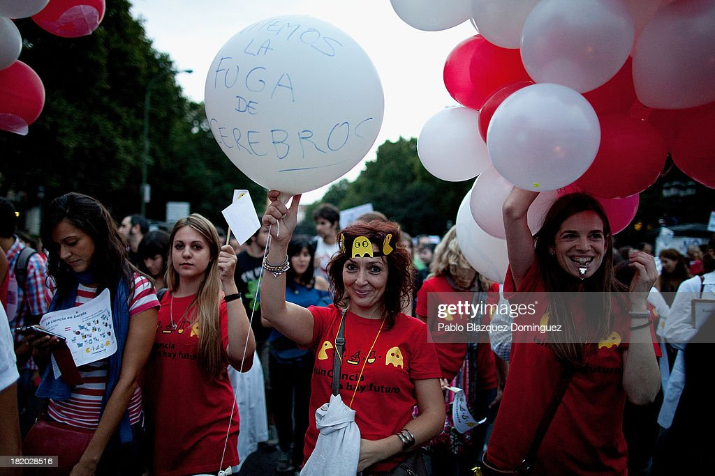 A woman (C) holds a balloon reading 'Let's avoid the brain drain' during a demonstration with other researchers against R&D cuts for sciences on September 27, 2013 in Madrid, Spain. Young Spanish scientists have called for a demonstration during the European Researchers' Night under the header, 'No Sciences, No Future', in response to cutbacks in research and development for Sciences. They claim that many Spanish researchers are leaving the country to find a jobs.
