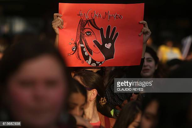 A woman holds a banner during a march in Santiago on October 19 to protest against violence against women and in solidarity for the brutal killing of...
