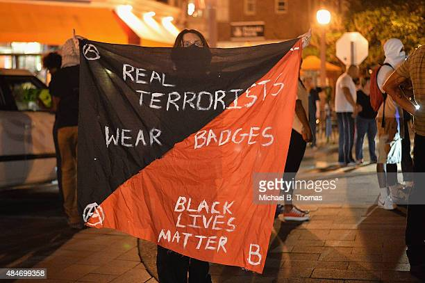 A woman holds a banner during a protest action through the Central West End of St Louis Missouri on August 20 2015 After a night of unrest sparked by...
