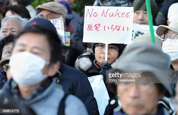 A woman holds a banner during a rally denouncing the Japanese government direction to resume nuclear power plants in front of the national Diet in...