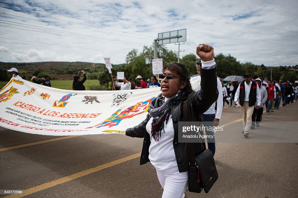 A woman holds a banner during the demonstrations, protesting the Educative Reform and the jailing of their leaders in Oaxaca, Mexico on June 26, 2016. At least 11 people killed and more of 100 people injured in Nochixtlan, Mexico.