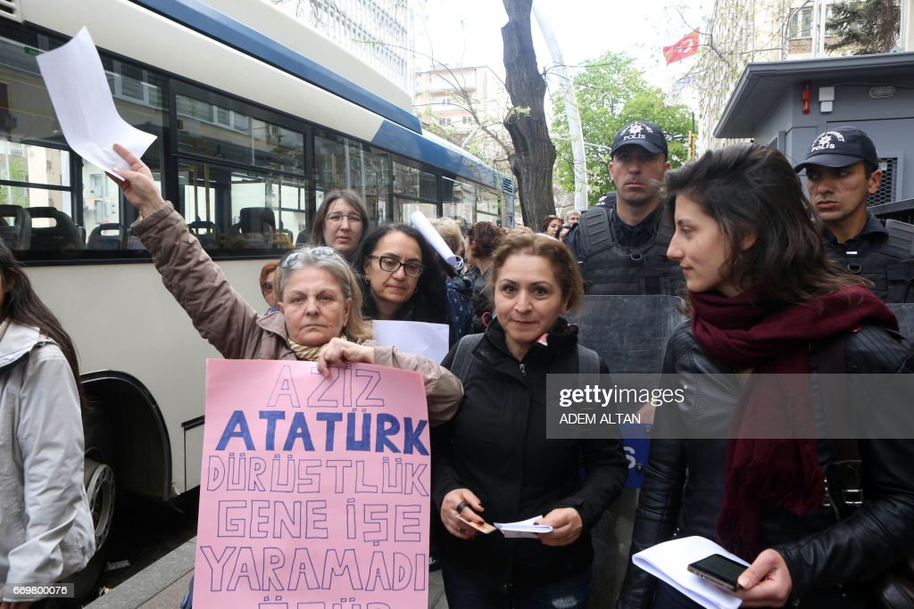 A woman holds a banner reading, 'Dear respected Ataturk, honesty didn't work again' as people queue outside the entrance of the High Electoral Board in Ankara, on April 18, 2017, in order to submit their personal appeal for the annulment of the referendum. Turkey's opposition on April 18, 2017 demanded the annulment of a contentious referendum that approved sweeping constitutional changes boosting President Recep Tayyip Erdogan's powers, claiming blatant vote-rigging. The European Union also urged a probe into the poll fraud claims after international observers voiced concerns. ALTAN