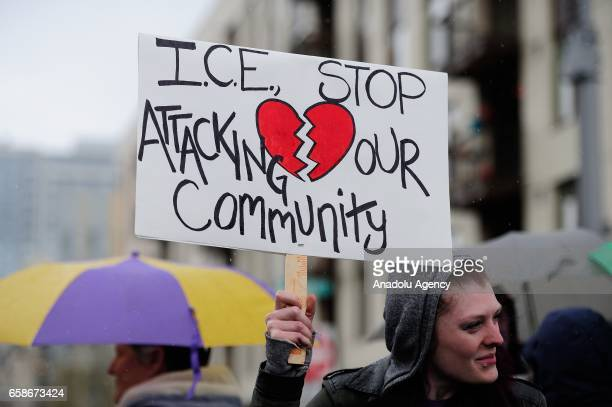 A woman holds a banner reading 'ICE stop attacking our community' during a protest outside the Immigration and Customs Enforcement building in...