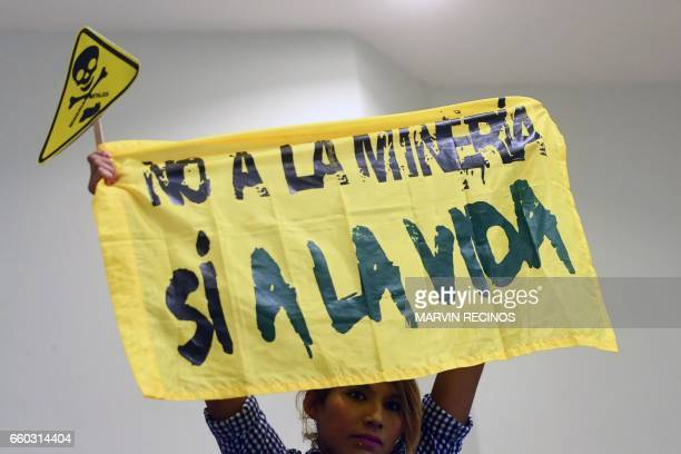 A woman holds a banner reading 'No to mining Yes to life' during a protest against mining at the Legislative Assembly in San Salvador on March 29...