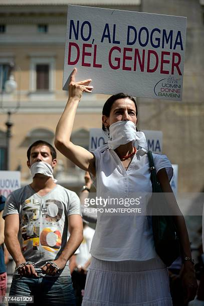 A woman holds a banner reading 'No to the dogma of gender' as a group of demonstrators stand in front of the italian parliament with mouth and hands...