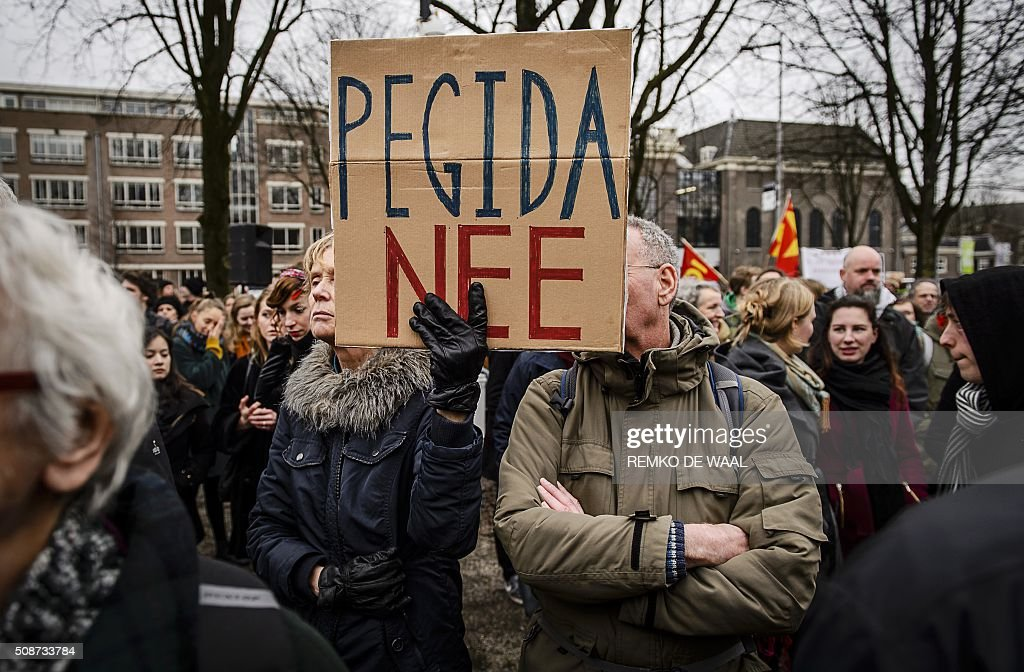 A woman holds a banner reading 'PEGIDA no' during a rally against the anti-Islamic political movement PEGIDA (Patriotic Europeans Against the Islamisation of the Occident) prior to a demonstration of the anti-immigrant PEGIDA movement in central Amsterdam, on February 6, 2016. / AFP / ANP / Remko de Waal / Netherlands OUT