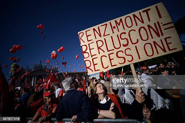 A woman holds a banner reading 'RenziMontiBerlusconi = recession' during a demonstration organised by Italian General Confederation of Labour union...