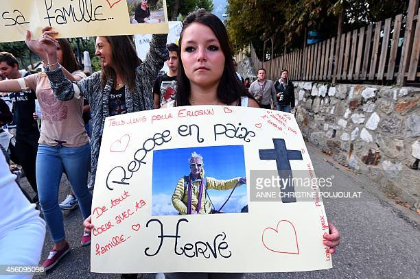 A woman holds a banner reading 'Rest in Peace Herve' as hundreds of people pay tribute to mountainguide Herve Gourdel who was beheaded by Jihadists...