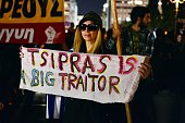 A woman holds a banner reading 'Tsipras is a big traitor' in front of the Greek parliament in Athens on October 16 while Greece's parliament is...