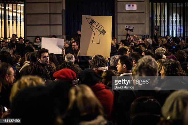 A woman holds a banner with a pencil painted during a gathering of people showing their support for the victims of the terrorist attack at French...