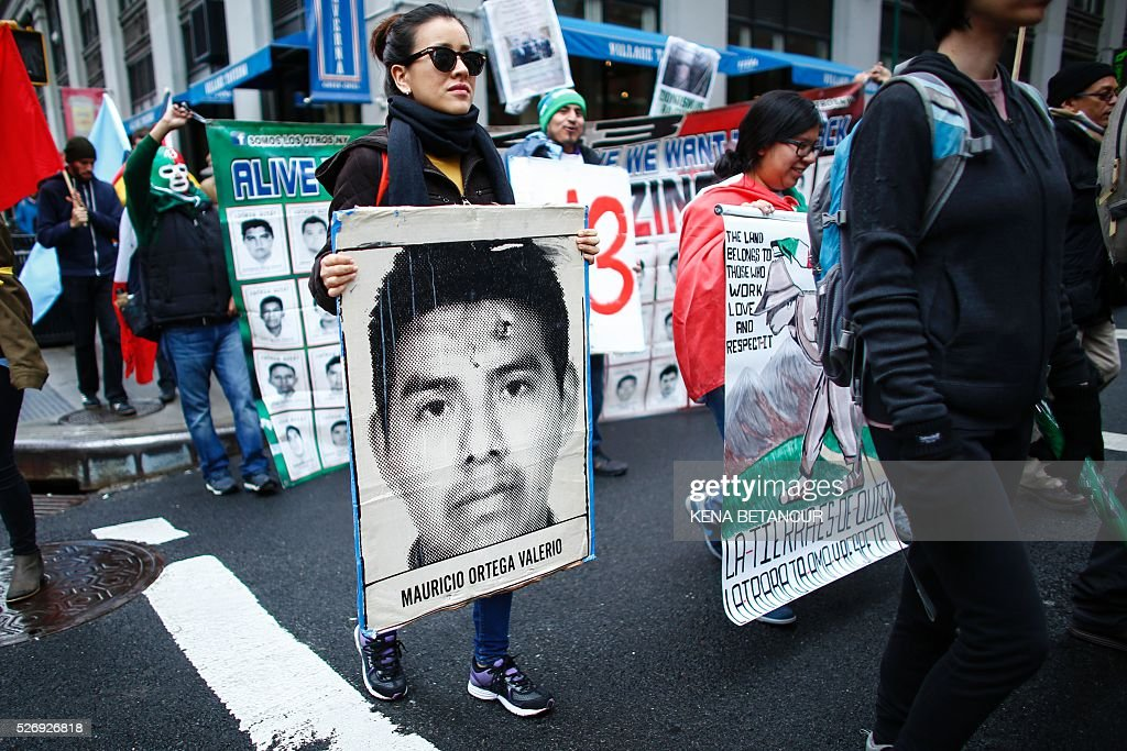 A woman holds a banner with the picture of one of the 43 Mexican Missing students as she takes part during the May Day demonstration in Washington Square Park on May 1, 2016 in New York. Thousands are expected to take part in May Day rallies across the country to supprot workers rights. / AFP / KENA