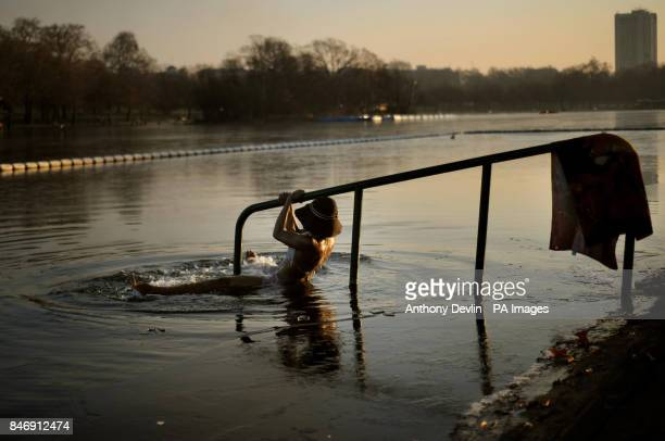 A woman holds a barrier as she dips into the water as swimmers brave the early morning cold weather to swim in the Serpentine in Hyde Park London as...