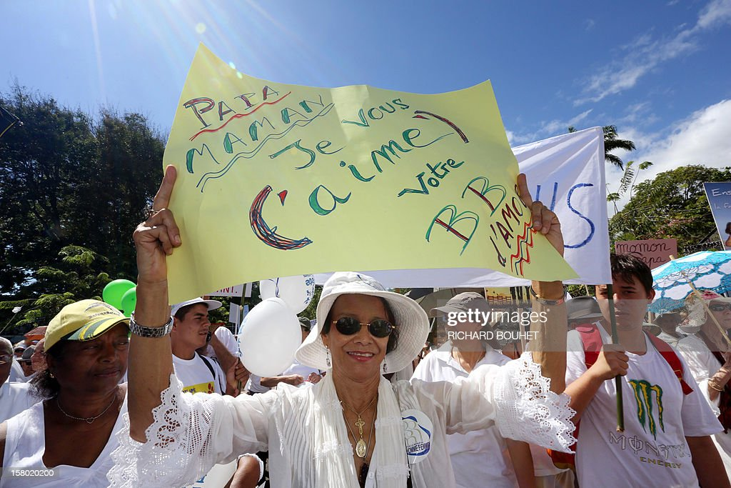 'Dad, Mum, I love you, your BB of love' during a demonstration called by a group of associations which support the same-sex marriage, on December 9, 2012, in Saint-Denis de la Reunion, on the French Indian Ocean island of La Reunion. France's Socialist government adopted on November 7, 2012 a draft law to authorise gay marriage and adoption despite fierce opposition from the Roman Catholic Church and the right-wing opposition. AFP PHOTO RICHARD BOUHET