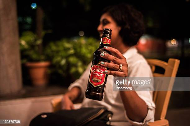 A woman holds a bottle of Fuller Smith Turner Plc London Pride beer for a photograph at a bar in New Delhi India on Thursday Sept 27 2012 Diageo Plc...