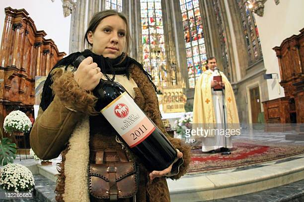 A woman holds a bottle of Saint Martin wine at the Church of St Peter and Paul in Brno South Moravia during the Saint Martin Wine festival on...