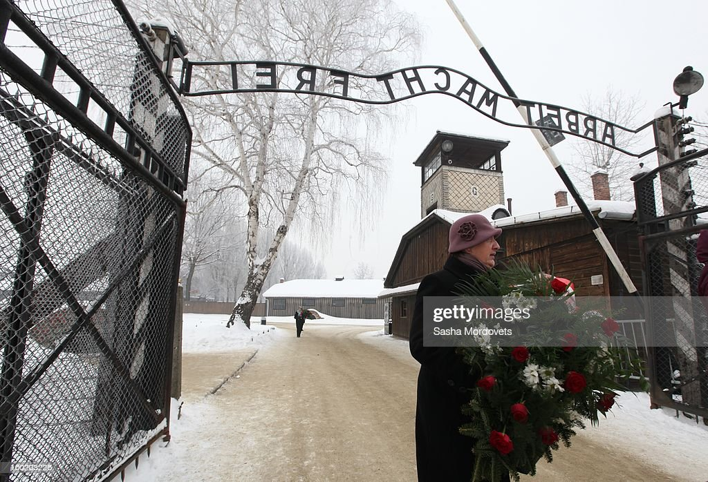 A woman holds a bouquet of flowers at the gate of the former Auschwitz Birkenau Nazi concentration camp January 27, 2013 near Oswiecim, Poland. A ceremony marked the 68th anniversary of the liberation of the camp during International Holocaust Remembrance Day.
