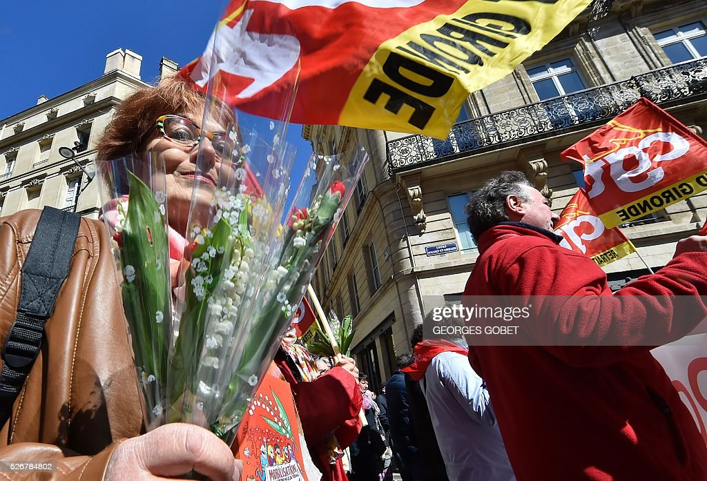 A woman holds a bouquet of lily of the valley as she demonstrates in the streets of Bordeaux during the traditional May Day rally on May 1, 2016. / AFP / GEORGES