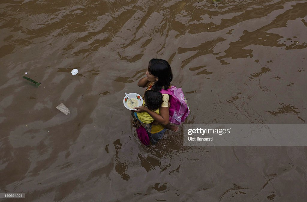 A woman holds a bowl of food and carries her daughter as she walks through floodwaters in Central Jakarta district on January 18, 2013 in Jakarta, Indonesia. According to the National Disaster Management Agency, about 50 percent of the capital is under water following the floods which have so far claimed eleven lives and displaced thousands of Indonesians.