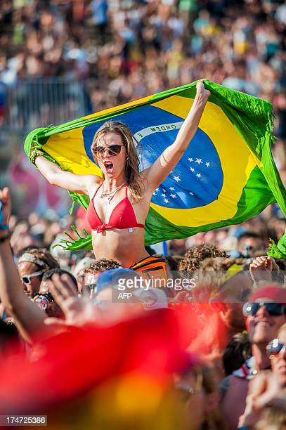 A woman holds a Brazilian national flag during the third day of the ninth edition of the Tomorrowland music festival on July 28 2013 in Boom AFP...