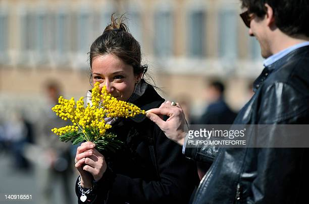 A woman holds a bunche of mimosaoutside the Italian Presidential palace the Quirinale to celebrate the International Women's day on March 8 2012 in...