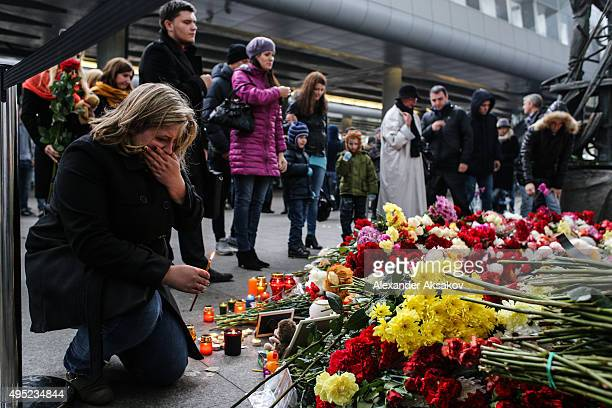 A woman holds a candle at a memorial for the victims of Airbus A321 crash at the Pulkovo Airport on November 1 2015 in St Petersburg Russia A Russian...