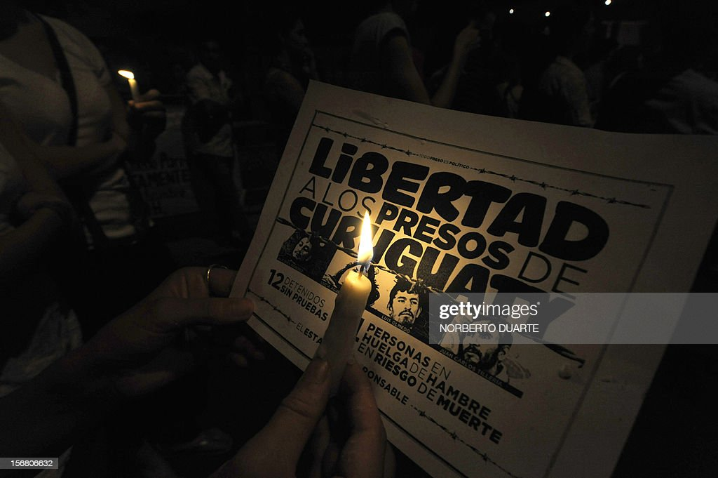 A woman holds a candle during a vigil of supporters of ousted Paraguayan President Fernando Lugo and relatives of jailed peasants, in demand of their freedom, on November 21, 2012 in Asuncion. Four peasants accused -alongside other eight people- of the death of six policemen past June 15 in Curuguaty, 250 km northeast of Asuncion, remain on hunger strike. 11 peasants died in the confrontation with the police during the eviction of a private property. AFP PHOTO/ Norberto Duarte