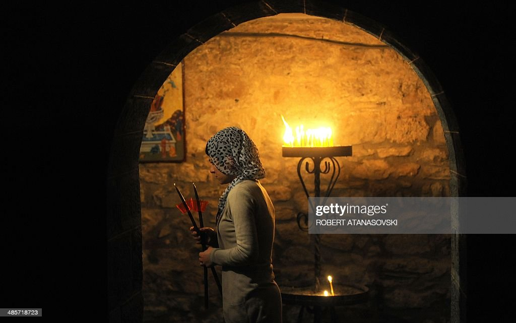 A woman holds a candle during an Easter service at the Saint Jovan Bigorski monastery, in Mavrovo, some 145 km west from the capital Skopje, in Macedonia, on April 20, 2014.The Macedonian Orthodox Church celebrated Easter, according to the Julian calendar.