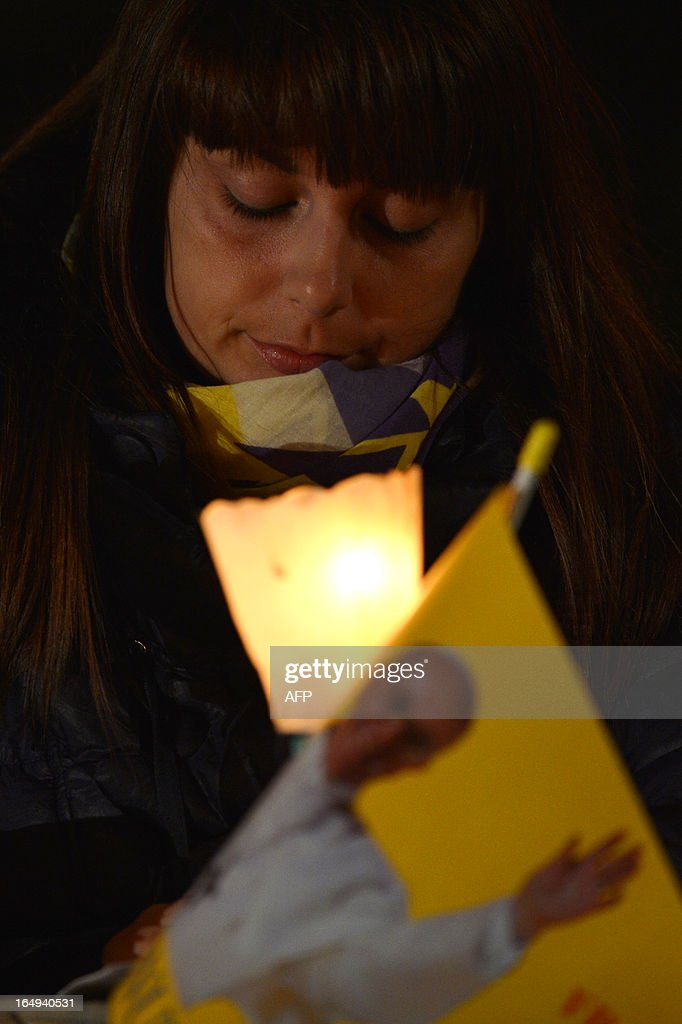 A woman holds a candle during the celebration of the Way of the Cross on Good Friday on March 29, 2013 at the Colosseum in Rome. Pope Francis presided over his first Good Friday which will culminate in a torch-lit procession at Rome's Colosseum and prayers for peace in a Middle East 'torn apart by injustice and conflicts'. AFP PHOTO / GABRIEL BOUYS