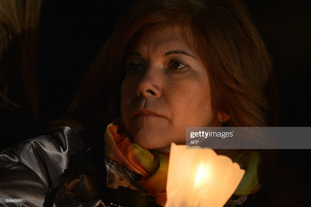 A woman holds a candle during the celebration of the Way of the Cross on Good Friday on March 29, 2013 at the Colosseum in Rome. Pope Francis presided over his first Good Friday which will culminate in a torch-lit procession at Rome's Colosseum and prayers for peace in a Middle East 'torn apart by injustice and conflicts'.