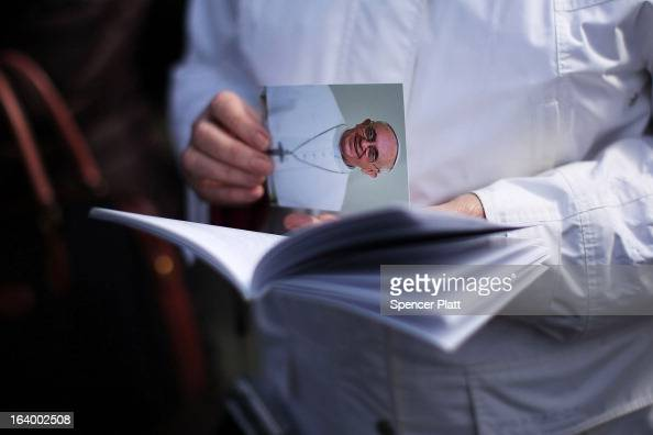 A woman holds a card with a picture of Pope Francis on it during the Inauguration Mass for Pope Francis in St Peter's Square on March 19 2013 in...