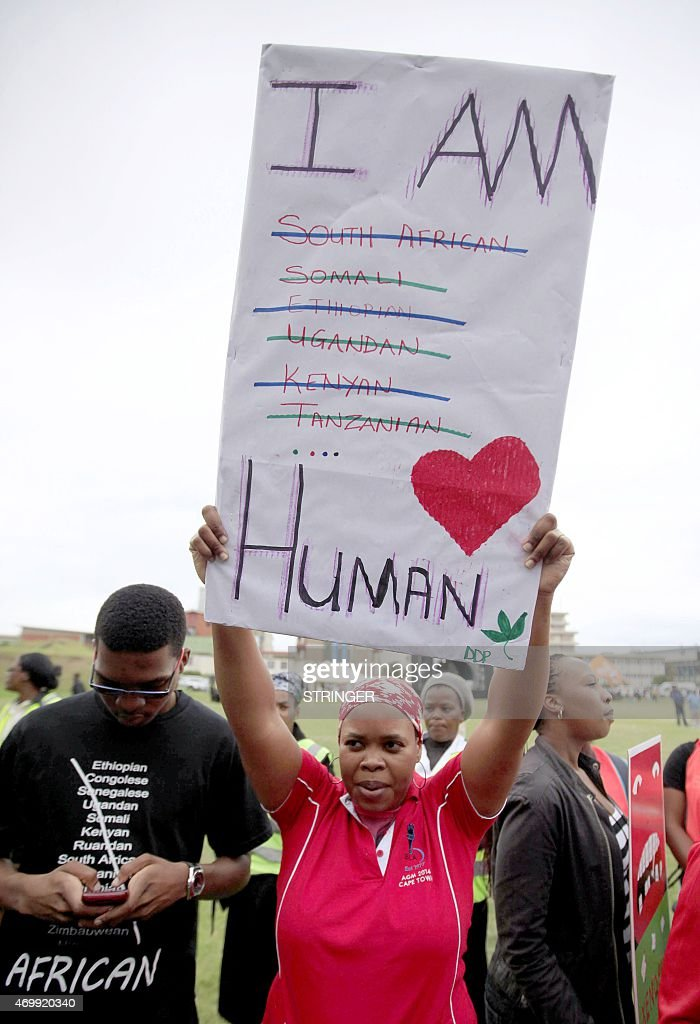 A woman holds a cardboard as she takes part in a 'peace march' against xenophobia attended by thousands of people in Durban on April 16 2015 South...