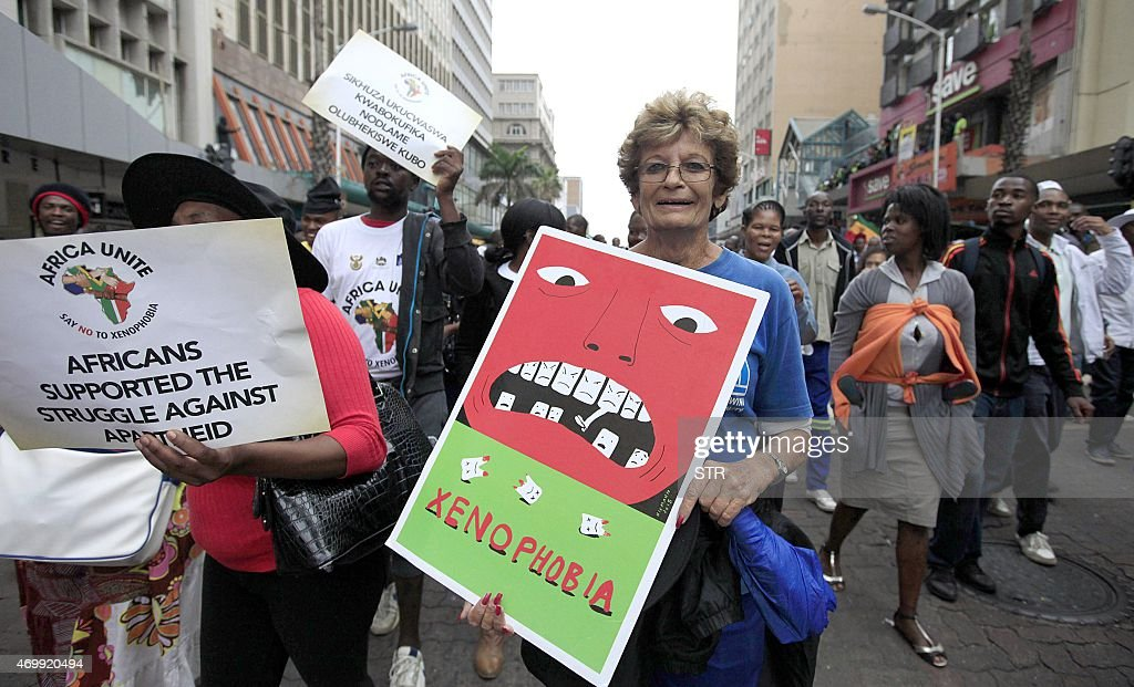 A woman holds a cardboard while taking part in a 'peace march' against xenophobia attended by thousands of people in Durban on April 16 2015 South...