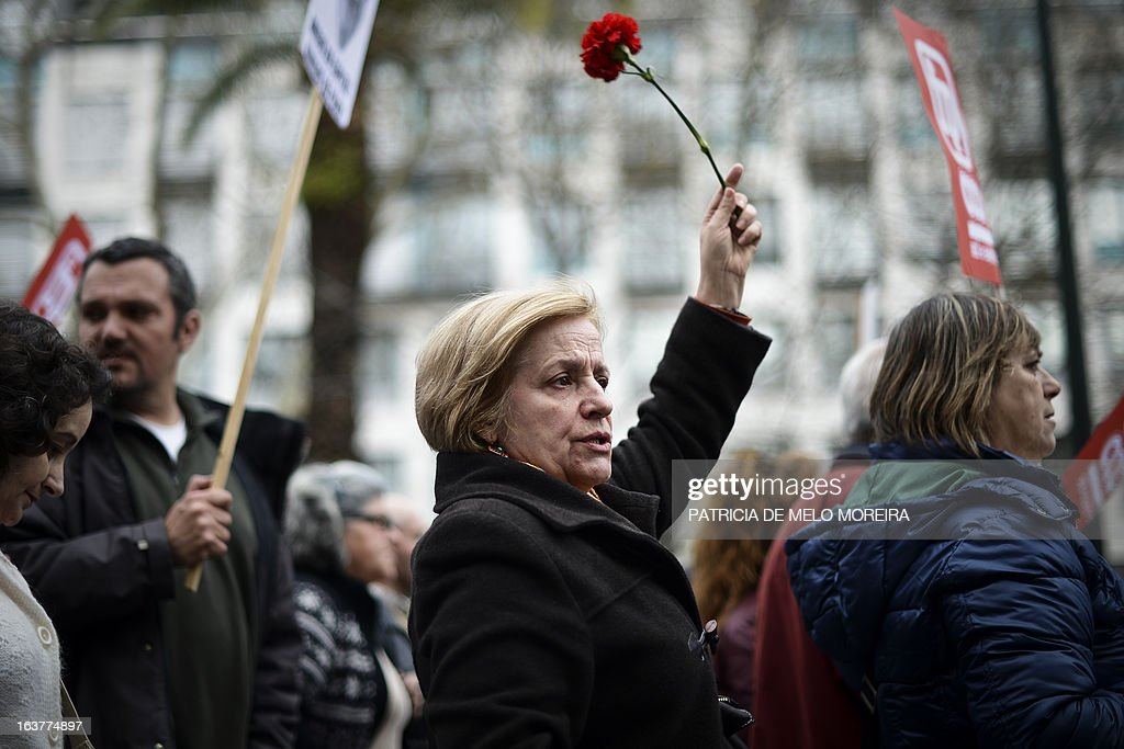 A woman holds a carnation and shouts slogans as she marches with thousands of people during a demonstration called by the unions Common Front, CGTP (General Confederation of the Portuguese Workers) and STAL (National Union of the Local and Regional Public Workers) against the austerity measures of the Portuguese government in Lisbon on March 15, 2013. Today the Finance Minister, Vitor Gaspar, said that the GDP (Gross Domestic Product) will drop 2.3%, that unemployment might reach 19% and the adjustment effort will have to continue for decades.'