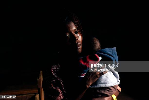 A woman holds a child after attending a mass celebrated in the Royal Kings International school in Freetown on August 20 2017 A week after Sierra...