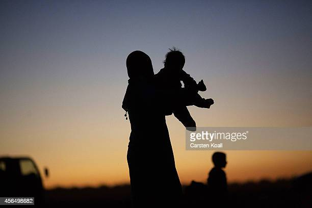 A woman holds a child after crossing the border from Syria into Turkey on October 1 2014 near Suruc Turkey Kurdish troops are engaged in a battle...