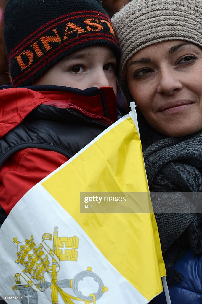 A woman holds a child and a Vatican's flag during Pope's first Angelus prayer at St Peter's square on March 17, 2013 at the Vatican. Pope Francis begins his papacy in earnest today ahead of his formal inauguration mass, with a weekly prayer address used by previous pontiffs to comment on international affairs. The pope's first Angelus prayer, delivered from a window high above St Peter's Square, is a chance for the first Latin American pontiff to begin to sketch out a more global vision for the role of the Roman Catholic Church.