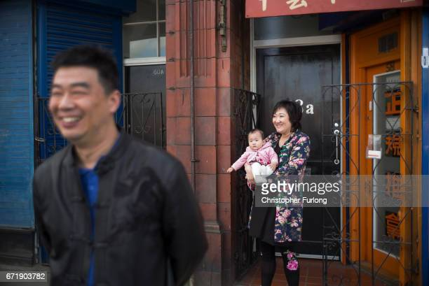 A woman holds a child as families and local residents watch the Manchester St George's Day parade through the streets on April 23 2017 in Manchester...