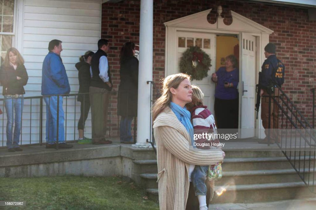 A woman holds a child as people line up to enter the Newtown Methodist Church near the the scene of an elementary school shooting on December 14, 2012 in Newtown, Connecticut. According to reports, there are about 27 dead, 18 children, after a gunman opened fire in at the Sandy Hook Elementary School. The shooter was also killed.