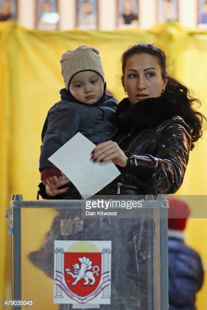 A woman holds a child as she casts her vote inside a polling station in Simferopol on March 16 2014 in Simferopol Ukraine Crimeans go to the polls...